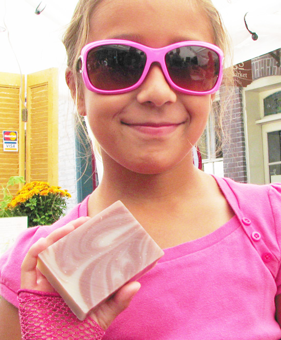 young girl in pink holding Herbaria Peppermint soap photo